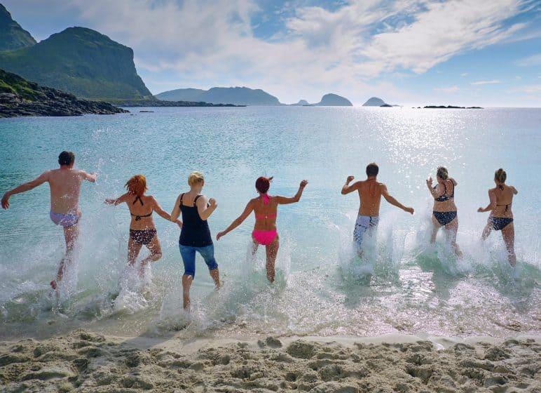 acht Menschen rennen ins Meer