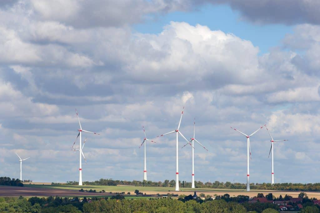 Windräder auf Feld mit wolkigem Himmel
