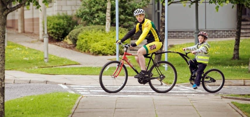 Mann auf Fahrrad mit Kind auf Fahrrad