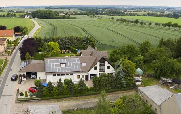 Luftaufnahme eines Hauses mit Photovoltaikanlage auf dem Dach
