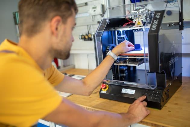 Auszubildender bedient einen 3D-Drucker während seines Unterrichts