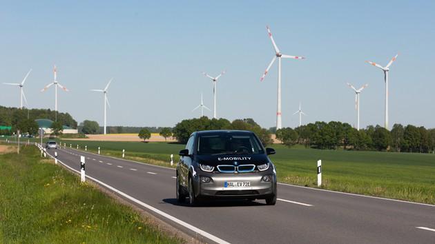 Elektroauto BMW i3 fährt auf einer Landstraße, im Hintergrund sind Windräder