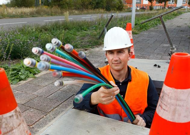 Mann mit Glasfaserkabeln in der Hand bei der Arbeit