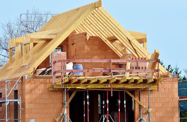 Haus im Rohbau mit Blick auf den Dachstuhl aus Holz