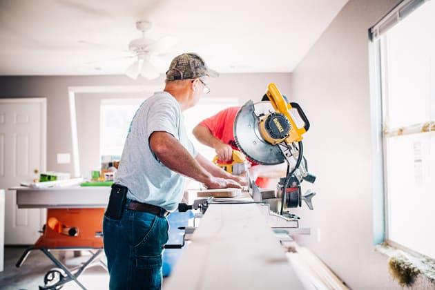Handwerker arbeiten mit einer Säge und schneiden eine Platte zurecht