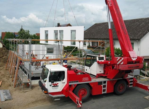 Zusammensetzung eines Fertigteilhauses auf einer Baustelle