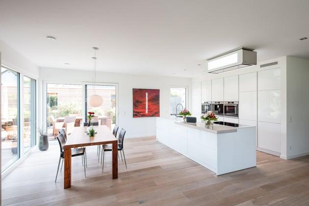 moderne Küche mit Kochinsel, Sitzecke und großem Fenster