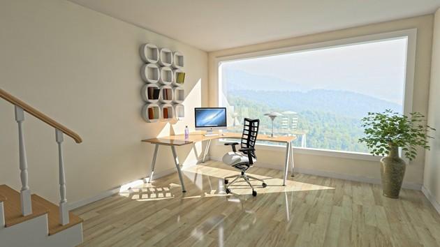 Schreibtisch steht vor großem, lichtdurchfluteten Fenster