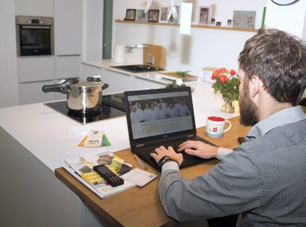 Mann sitzt in Küche und arbeitet