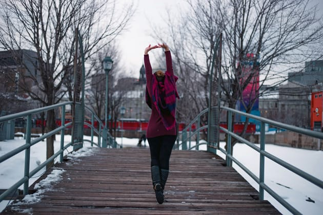 Frau läuft über eine Brücke und streckt sich dabei