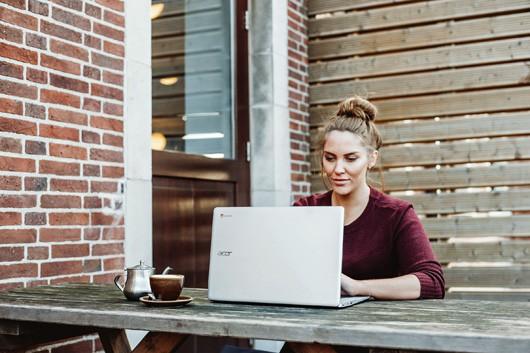 Frau arbeitet am Laptop, Teekanne und Teetasse stehen neben ihr