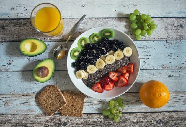 Frühstück mit Obst, Avocado, Brot und Saft