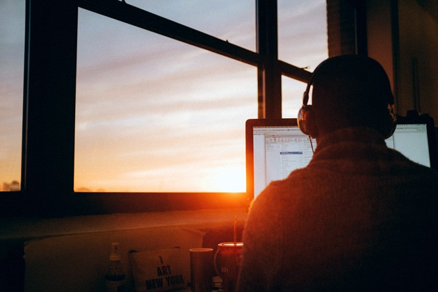 Mann sitzt bei Sonnenaufgang am Schreibtisch