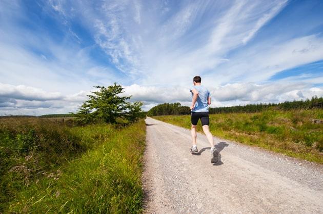 Mann rennt auf einem Weg zwischen Wiesen