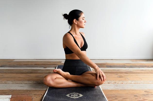 Frau sitzt auf einer Matte und macht Yoga