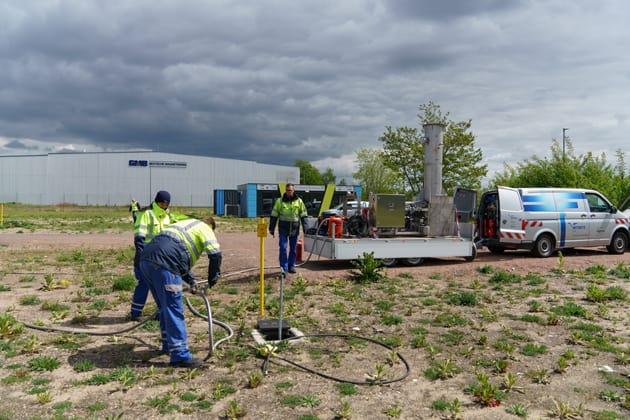 mehrere Männer in Arbeitskleidung führen Tests beim Projekt HYPOS:H2-Netz im Chemiepark Bitterfeld-Wolfen durch, im Hintergrund steht ein Fahrzeug mit Anhänger und einer Wasserstofffackel