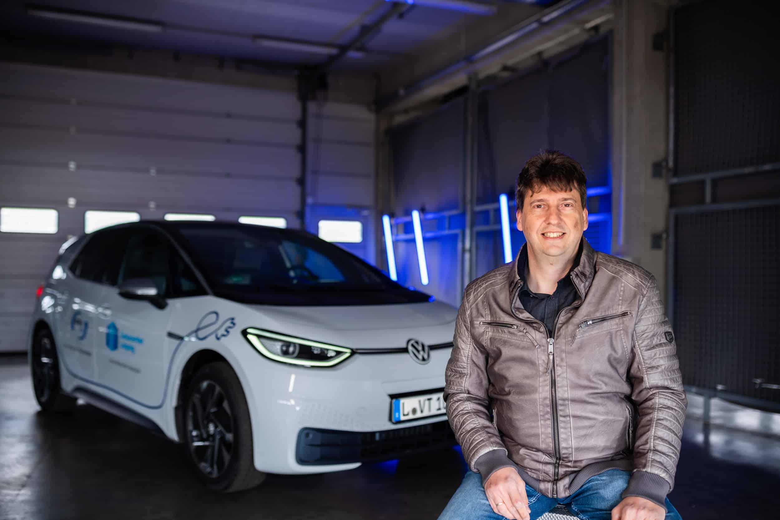 Michael Freitag, Projektleiter envia TEL für Datacenter, vor einem E-Auto