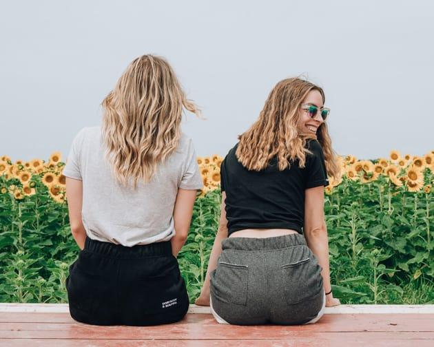Zwei Mädchen sitzen vor einem Sonnenblumenfeld