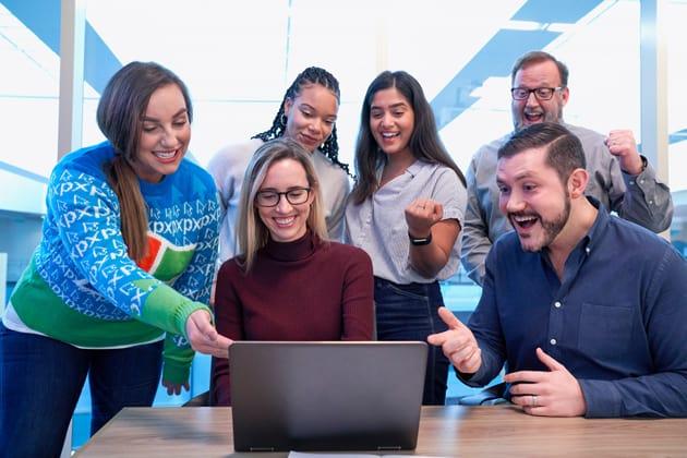 Studentengruppe schaut auf einen Laptop