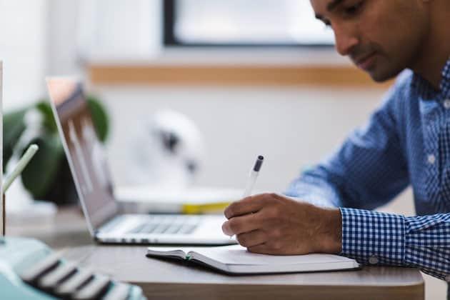 Mann vor Laptop schreibt mit einem Stift in ein Notizbuch