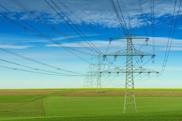 Stromleitungen auf einer Wiese/Feld vor blauem Himmel