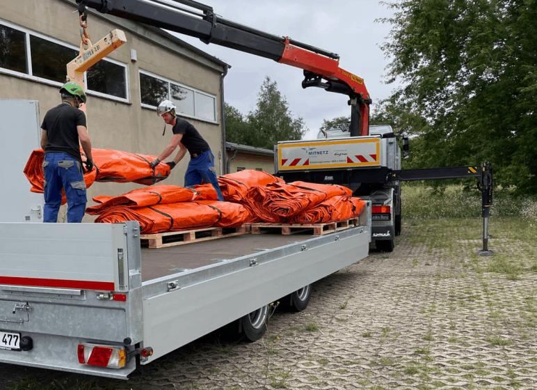 MITNETZ STROM Mitarbeiter machen das Hochwasserschutzsystem Beaver fertig für den Transport.